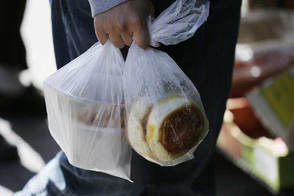 In this photo taken Tuesday, Sept. 20, 2016, a man carries food through Chinatown in a pair of plastic bags in San Francisco. California voters are considering a November referendum that would uphold or overturn a statewide ban on single-use plastic carryout bags, and another ballot initiative that would require fees collected from retail customers for alternative bags be put in an environmental fund. In 2007, San Francisco banned plastic shopping bags, setting off a movement that�s led to nearly half the state and its biggest cities to do the same. (AP Photo/Eric Risberg)
