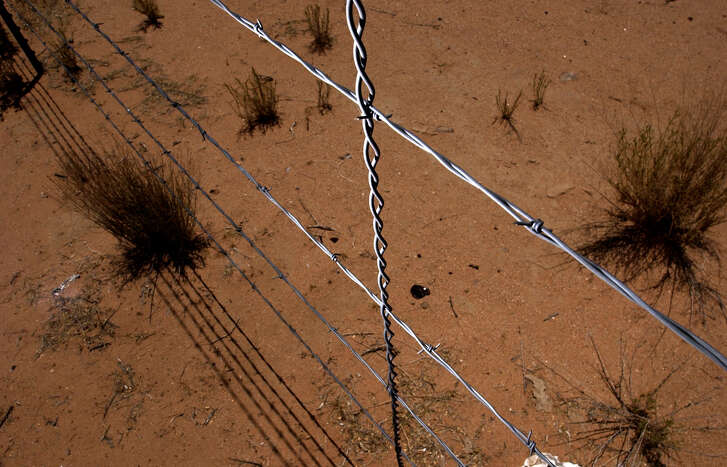 A four string barbed wire fence separates Mexico and the United States while on the Tohono O'Odham Reservation, Tuesday, June 17, 2003 near Sells, Arizona. CHRISTOBAL PEREZ/HOUSTON CHRONICLE.