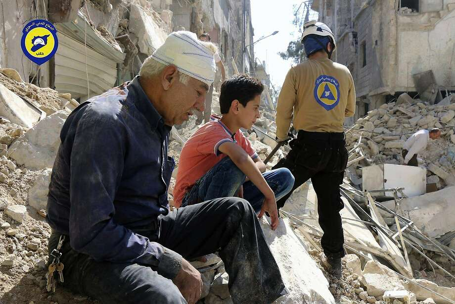A picture provided by Syrian Civil Defense shows eastern Aleppo residents sitting among rubble Tuesday. Photo: Uncredited, Associated Press