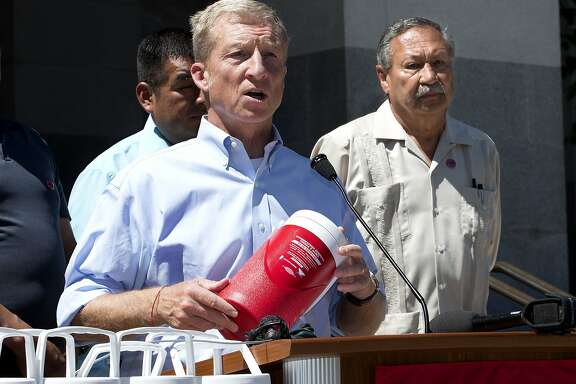 Philanthropist Tom Steyers, center, holds one of more than 1,000 water bottles being given to farm workers to help deal with the summertime heat, Wednesday, June 29, 2016, in Sacramento, Calif. Steyers', Next Gen organization, and the United Farm Workers, President Arturo Rodriguez, right, announced the collaboration between Next Gen and the UFW to provide farm workers throughout the state thousands of half-gallon bottles printed with information about workers' rights and California laws aimed at preventing heat deaths. (AP Photo/Rich Pedroncelli)