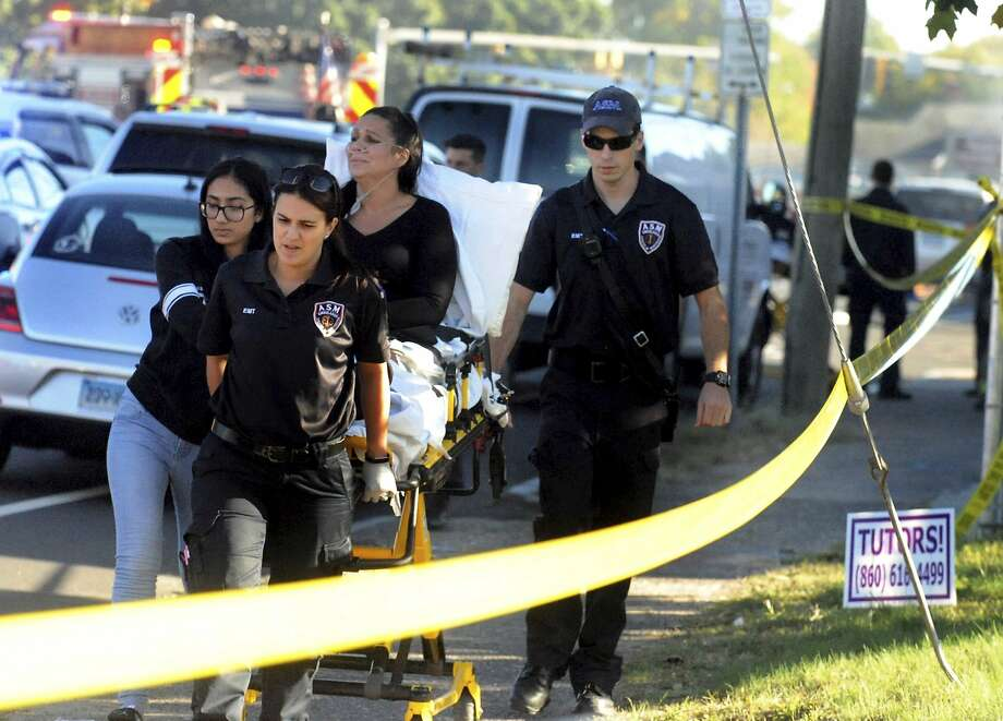 A woman who was injured on the ground is taken away from the crash site Tuesday in East Hartford, Conn. A student pilot was killed in the crash, and his instructor was badly burned. Photo: JIM MICHAUD, Associated Press