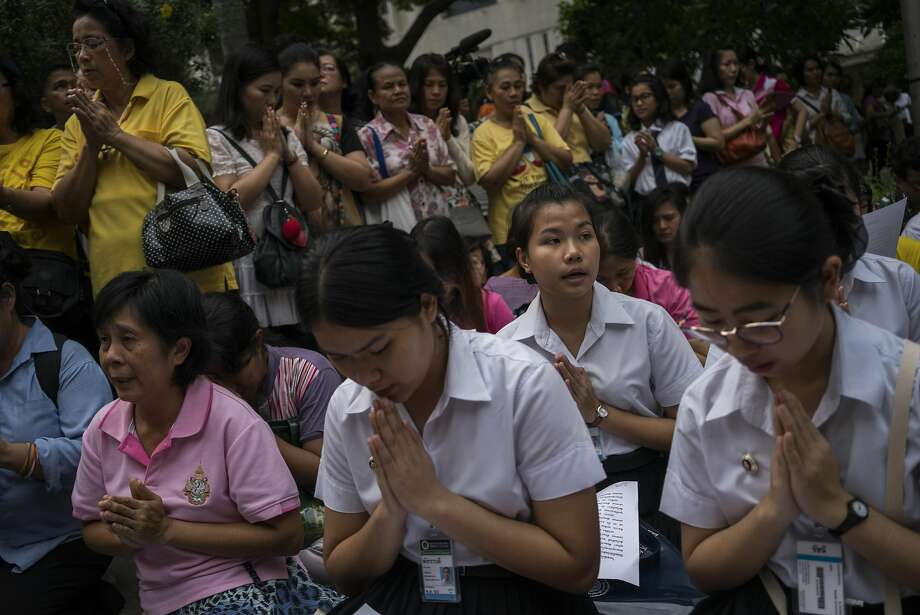 Supporters pray for Thailand's King Bhumibol Adulyadej outside the hospital where he is being treated in Bangkok. Many Thais wore pink to promote the 88-year-old king's well-being. Photo: ADAM DEAN, NYT