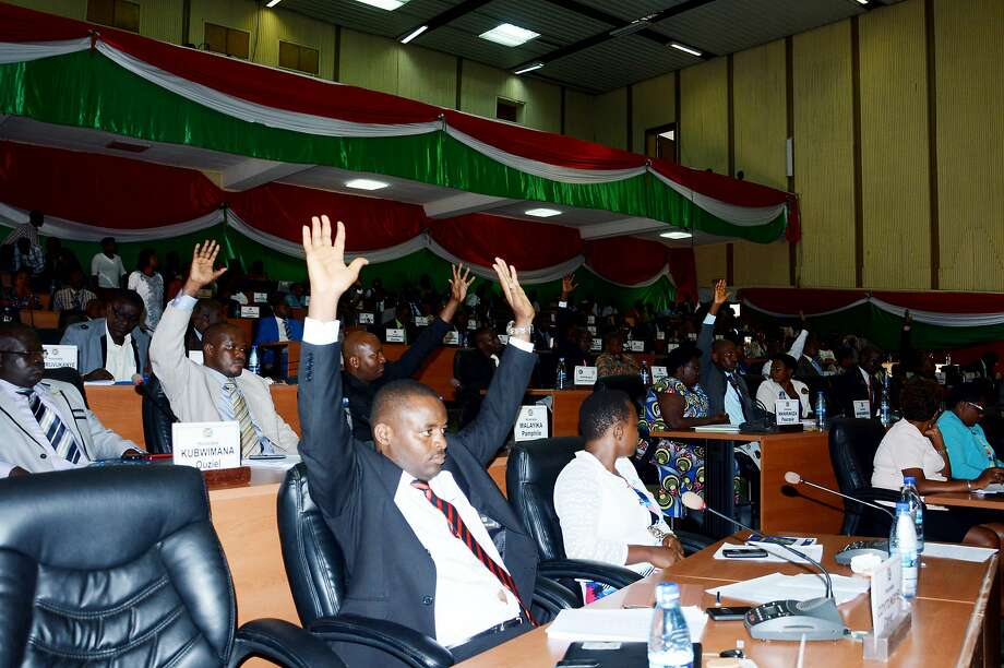"Members of Burundi's lower house of parliament raise their arm to vote on October 12, 2016 in Bujumbura, for the withdrawal of the International Criminal Court (ICC) from the capital, after the UN began an enquiry into human rights abuses in the turbulent nation. The draft law was passed with 94 votes in favour, two against and 14 abstentions. It will next go to the Senate -- also dominated by the ruling party -- before being approved by President Pierre Nkurunziza. In April, ICC prosecutor Fatou Bensouda said she was conducting a ""preliminary examination"" of the situation in Burundi -- the first step towards a full investigation and possible prosecutions -- looking into allegations including murder, torture, rape and forced disappearances. / AFP PHOTO / ONESPHORE NIBIGIRAONESPHORE NIBIGIRA/AFP/Getty Images Photo: ONESPHORE NIBIGIRA, AFP/Getty Images"