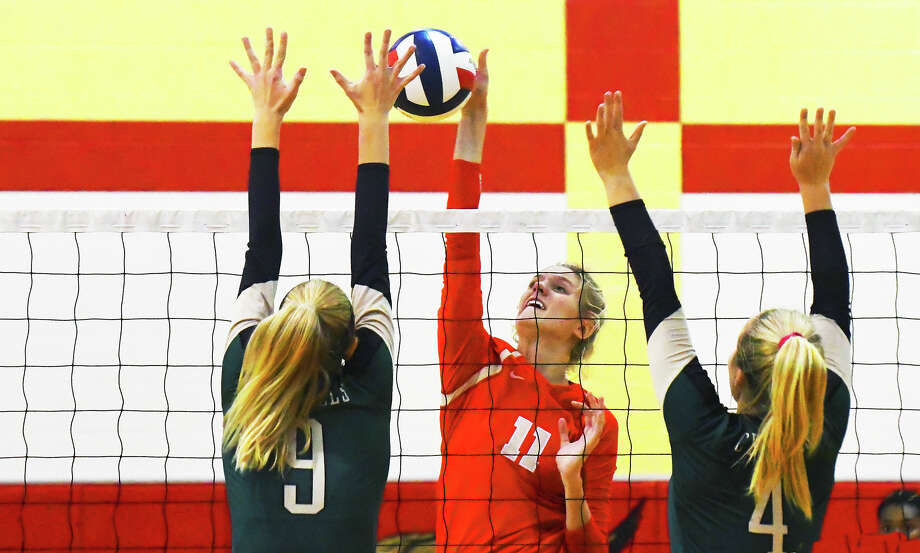 Cy Woods junior middle blocker Cate Reese, center, records one of her two solo blocks against Cy Falls Tuesday night at Cypress Woods High School. Reese also had 10 kills in the three-set victory. Photo: Tony Gaines / HCN