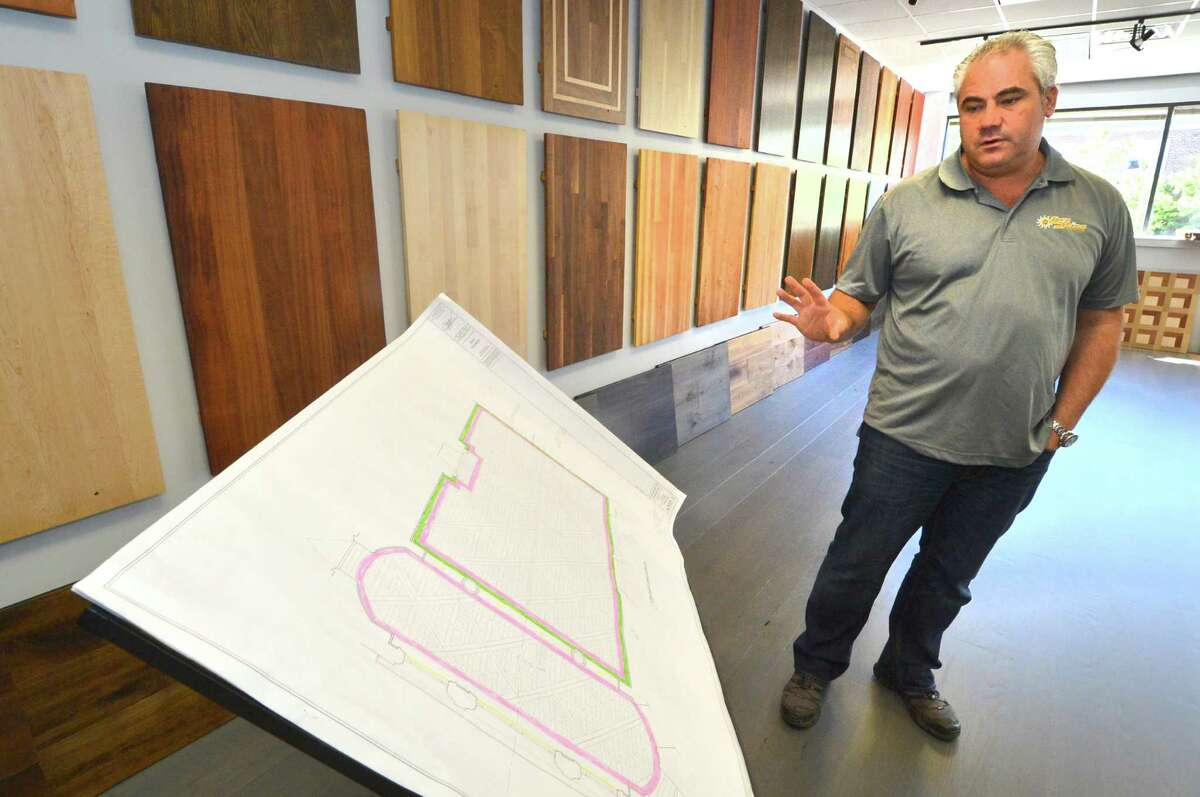 Razan Tata, CEO of SunShine Floors looks over plans for a clients new floor installation in his new Norwalk Conn. showroom with samples of the different types of wood and finishes available for new hardwood floors , on Tuesday October 11, 2016.