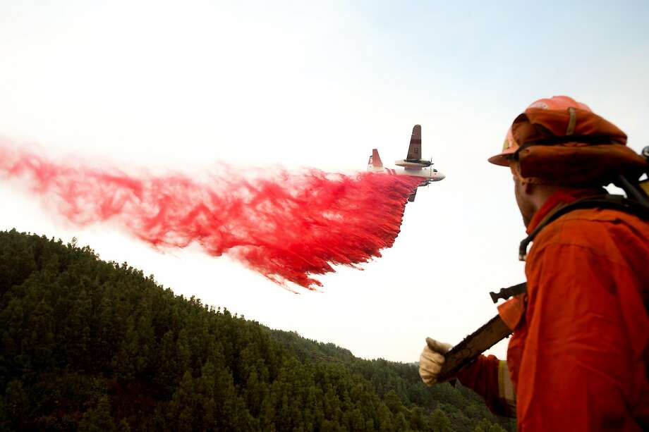 An inmate firefighter watches as an air tanker drops retardant while battling a wildfire near Morgan Hill, Calif., on Wednesday, Sept. 28, 2016. A growing and destructive wildfire moved toward remote California homes in the Santa Cruz Mountains on Wednesday as it scorched its way through bone-dry brush and trees. (AP Photo/Noah Berger) Photo: Noah Berger, Associated Press
