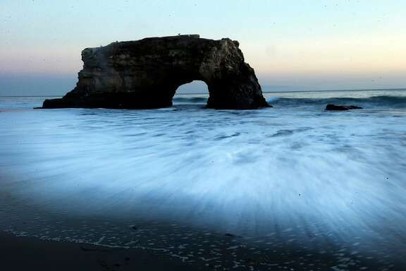 AP10ThingsToSee - In this picture made with a long exposure, waves move on the shore as the sun sets at Natural Bridges State Beach on Wednesday, Feb. 19, 2014, in Santa Cruz, Calif. (AP Photo/Marcio Jose Sanchez, File)