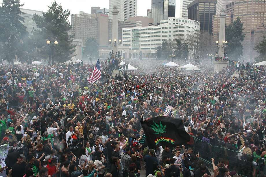People smoke marijuana at a 2013 rally in Denver. Police used tracking software to monitor the gathering. Photo: Brennan Linsley, Associated Press