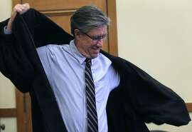 C.W. Nevius dons a ceremonial robe for his role as a marriage commissioner for a day before conducting weddings at City Hall in San Francisco, Calif. on Friday, Sept. 4, 2015.