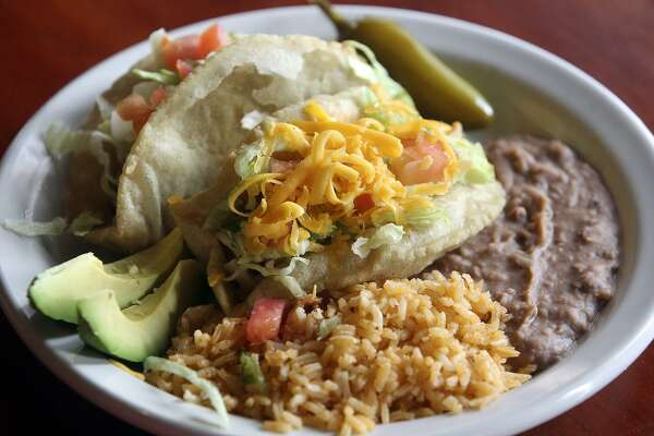 "Ray's Drive Inn, an old-school drive-in, serves what ""The Tacos of Texas"" calls ""The San Antonio Iconic Taco."" ""While the puffy taco is not consumed by the masses, it's what sets the San Antonio taco scene apart,"" write authors Mando Rayo and Jarod Neece."