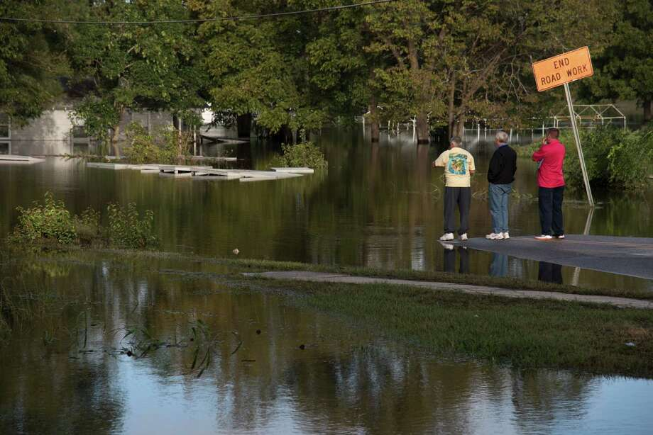 People in Lumberton, N.C., look out towards West 5th Street, which is covered by floodwaters caused by rain from Hurricane Matthew.i Photo: Mike Spencer, FRE / FR171472 AP