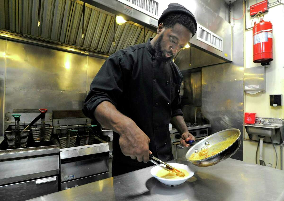 Jean Gabriel, co-owner/chef of Soul Tasty, plates Cajun Shrimp and Grits (below), one of the signature dishes for the new soul food restaurant in Stamford.