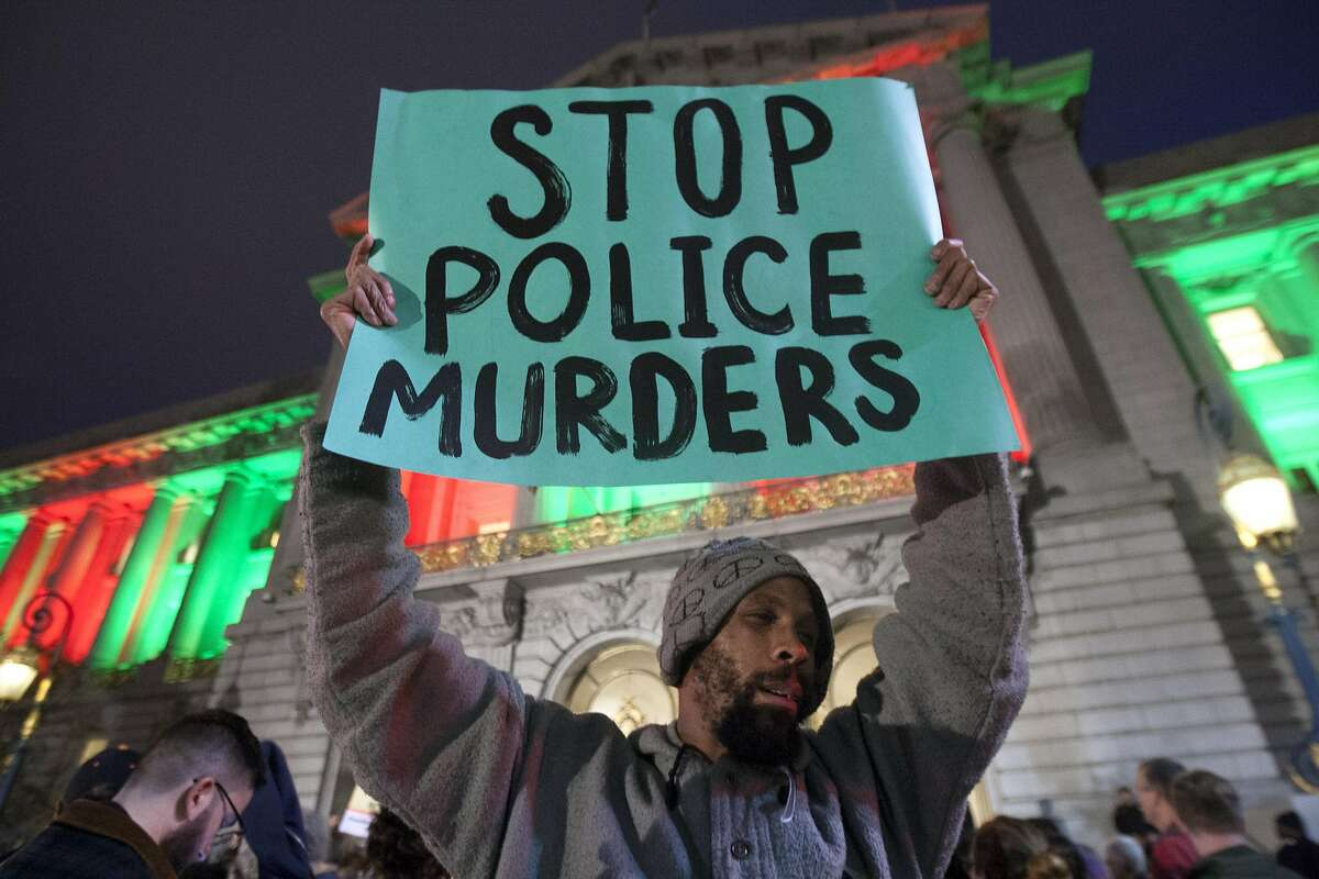 Hundreds of people protest outside San Francisco City Hall, Wednesday, Dec. 9, 2015, in San Francisco, Calif. The S.F. Police Commission met inside City Hall and talked about the possibility of equipping police officers with Tasers following the fatal shooting of Mario Woods. It's a proposal that was turned down twice by the commission in recent years. Woods' case has brought the proposal back. Woods was shot and killed by police officers after police say Woods was armed with a knife and walked toward officers.