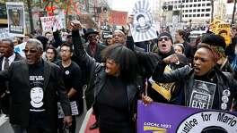 Deja (center) and Cassandra Grant (right) lead protesters demanding justice for Mario Woods, the Bayview man shot and killed by police nearly two months ago, on a march down Market Street to the site of Super Bowl City in San Francisco, Calif. on Saturday, Jan. 30, 2016.