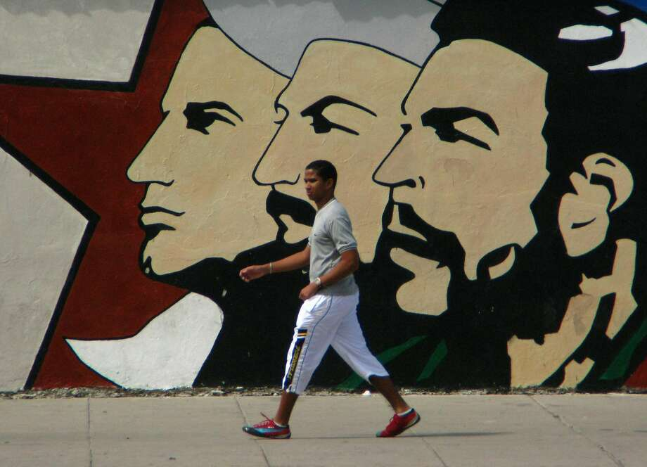 A Cuban man walks under the gaze of the leaders of La Revolucion, one of many murals meant to inspire patriotism. (Spud Hilton / The Chronicle) Photo: Spud Hilton, SAN FRANCISCO CHRONICLE