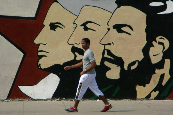 A Cuban man walks under the gaze of the leaders of La Revolucion, one of many murals meant to inspire patriotism. (Spud Hilton / The Chronicle)