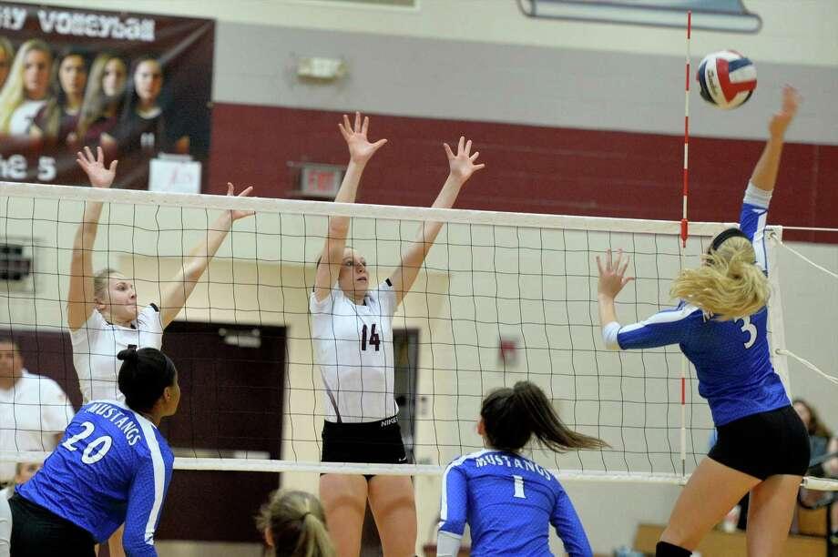 Blair Koepke (5) and Danyle Courtley (14) of Cinco Ranch try to block a shot made by Diane Hoff (3) of Taylor during the third set of a high school volleyball game between the Cinco Ranch Cougars and Katy Taylor Mustangs on October 11, 2016 at Cinco Ranch High School, Katy, TX. Photo: Craig Moseley, Houston Chronicle / ©2016 Houston Chronicle