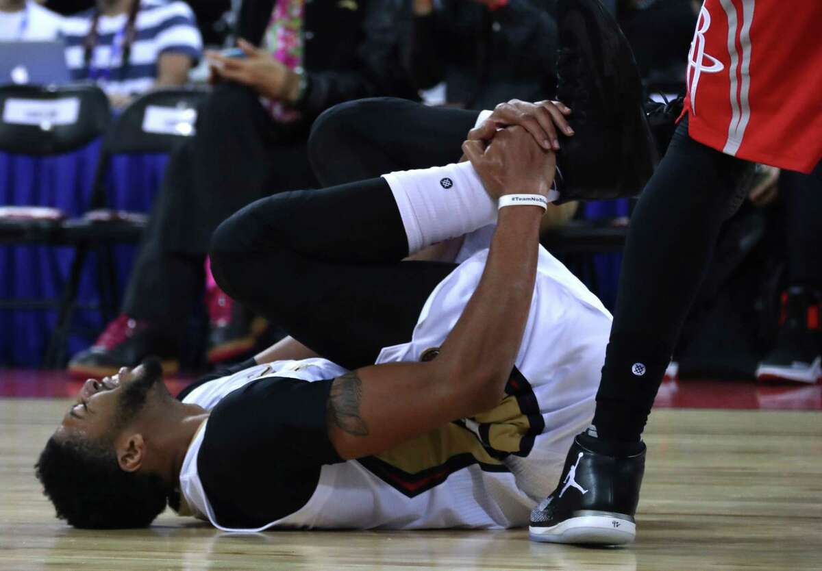 Anthony Davis of the New Orleans Pelicans reacts in pain as he injures his right ankle during a preseasons match against Houston Rockets in Beijing, China, Wednesday, Oct. 12, 2016. Davis fell to the court early in the first quarter of Wednesday's game in Beijing, the last of the NBA's two exhibitions in China. He re-entered the game briefly, but soon walked to the locker room. (AP Photo/Ng Han Guan)