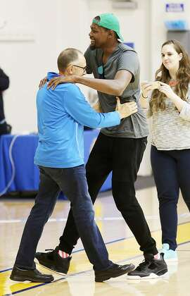 Kevin Durant embraces Golden State Warriors assistant coach Ron Adams before a news conference about Durant joining the Warriors at the NBA basketball team's practice facility, Thursday, July 7, 2016, in Oakland, Calif. (AP Photo/Beck Diefenbach)