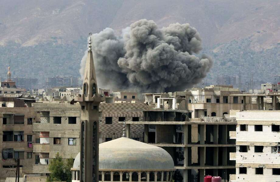 Smoke rises from buildings on Wednesday following airstrikes on Damascus' rebel-held eastern suburb of Zamalka. Photo: AMER ALMOHIBANY, Stringer / AFP or licensors
