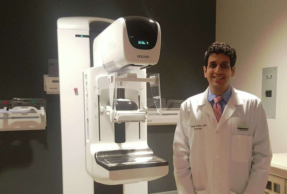 Dr. Chirag Parghi, director of The Breast Center at Kingwood Medical Center, stands next to the new 3D mammography system during the Breast Center open house Oct. 11.