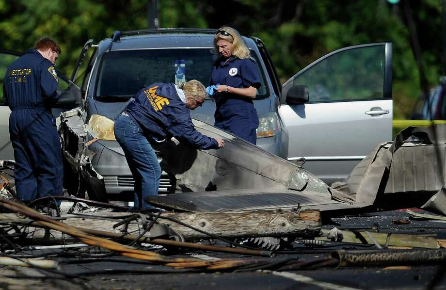 Investigators look at the remains of a small plane in East Hartford, Conn., on Wednesday, a day following the plane's crash. Officials said the deadly crash might have been intentional, but have ruled out terrorism.  Photo: Jessica Hill, FRE / FR125654 AP