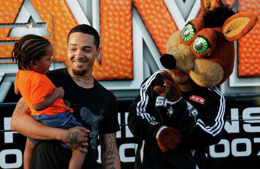 The Spurs Coyote waves to two-year-old Jaylen Martinez (left) who was a bit apprehensive to be photographed with the mascot while being held by his father, Tremayne Pete, during a Spurs-themed party by H-E-B celebrating more than 50 years on the city's Eastside complete with the Spurs Coyote, Team Energy and the Silver Dancers. The Sam Houston High School marching band also joined the celebration filling the late afternoon sky with music as patrons of the store slowly arrived to be treated to food and drink. To top off the event and to show their commitment to the area, H-E-B will be making a $50,000 donation to two organizations in the area, according to an official press release. The event was held at the H-E-B store located at 1012 South W.W. White Road.
