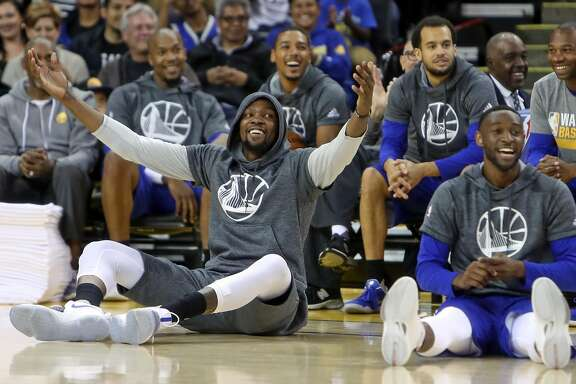 Golden State Warriors' Kevin Durant and Ian Clark laugh as rookies sing during open practice at Oracle Arena in Oakland, Calif., on Wednesday, October 12, 2016.