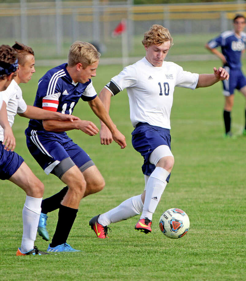 Seth Stapleton/Huron Daily Tribune   Bad Axe's Tyler Gilbert (10) handles the ball in front of USA's Harrison Cramer (11) during the first half of the Hatchets' 3-1 victory, Wednesday, in Bad Axe.