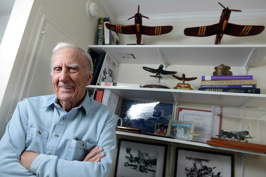 Nick Mainiero, a pilot in the U.S. Marine Corps fighter squadron VMF 441 during WWII, poses near some of his memorabilia at his home in Bridgeport. The former Marine World War II Corsair pilot and ex-head of Sikorsky Memorial Airport was honored by the Bridgeport City Council in 2014. Photo: Autumn Driscoll / File Photo / Connecticut Post