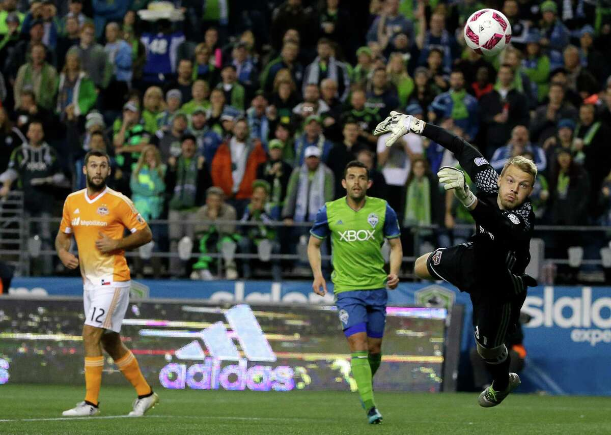 Houston Dynamo goalkeeper Joe Willis, right, dives for a the ball during the second half of the team's MLS soccer match against the Seattle Sounders, Wednesday, Oct. 12, 2016, in Seattle. The match ended in a scoreless tie. (AP Photo/Ted S. Warren)
