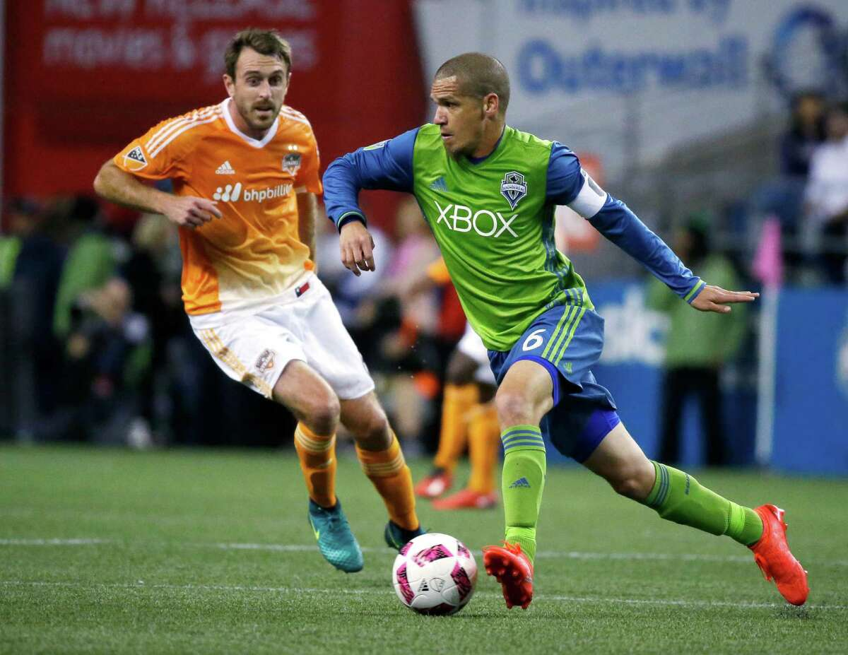 Seattle Sounders midfielder Osvaldo Alonso, right, drives against Houston Dynamo's Eric Alexander during the first half of an MLS soccer match, Wednesday, Oct. 12, 2016, in Seattle. (AP Photo/Ted S. Warren)