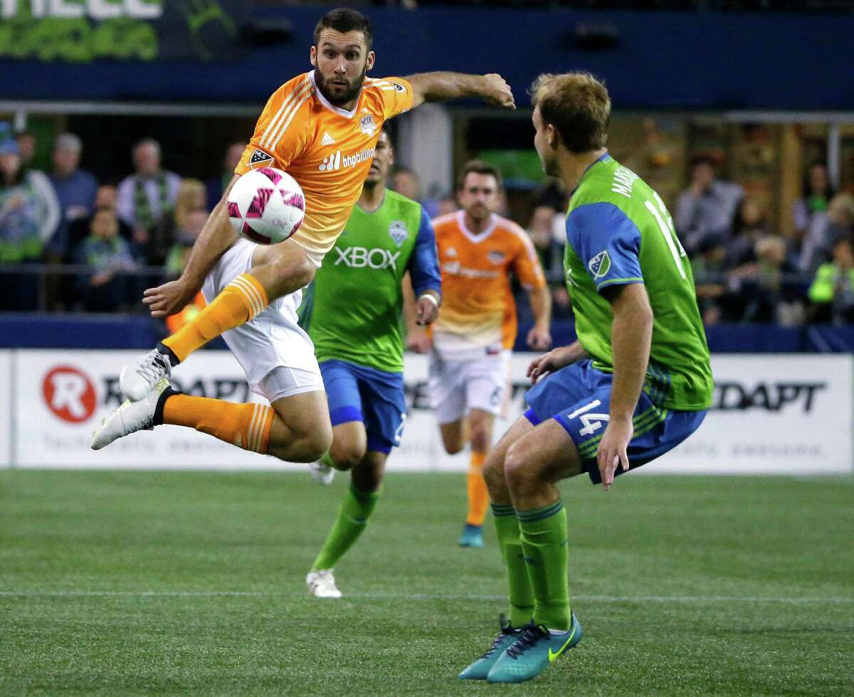 Houston Dynamo forward Will Bruin, left, leaps to make a kick against Seattle Sounders defender Chad Marshall, right, during the first half of an MLS soccer match, Wednesday, Oct. 12, 2016, in Seattle. (AP Photo/Ted S. Warren)