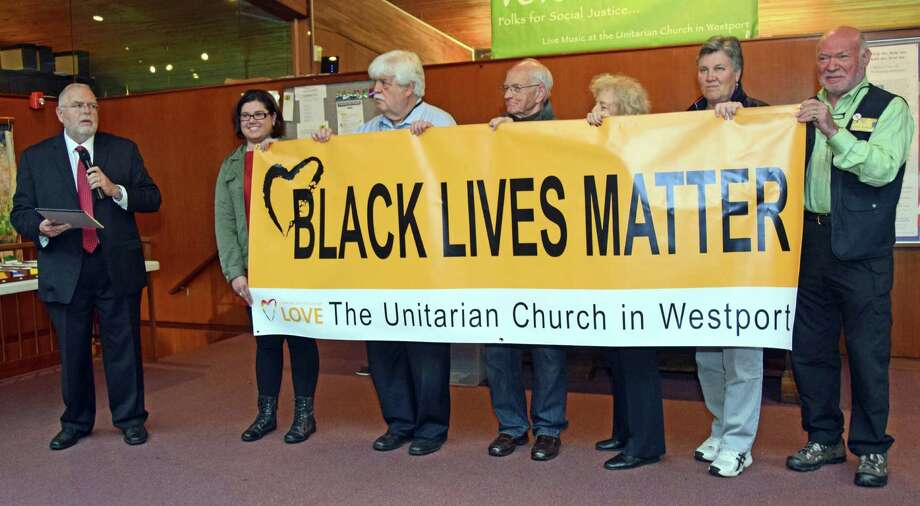 The Rev. John Morehouse, left, senior minister at the Unitarian Church in Westport, dedicates the Black Lives Matter banner while members of the congregation hold it. Photo: Contributed Photo / Westport News