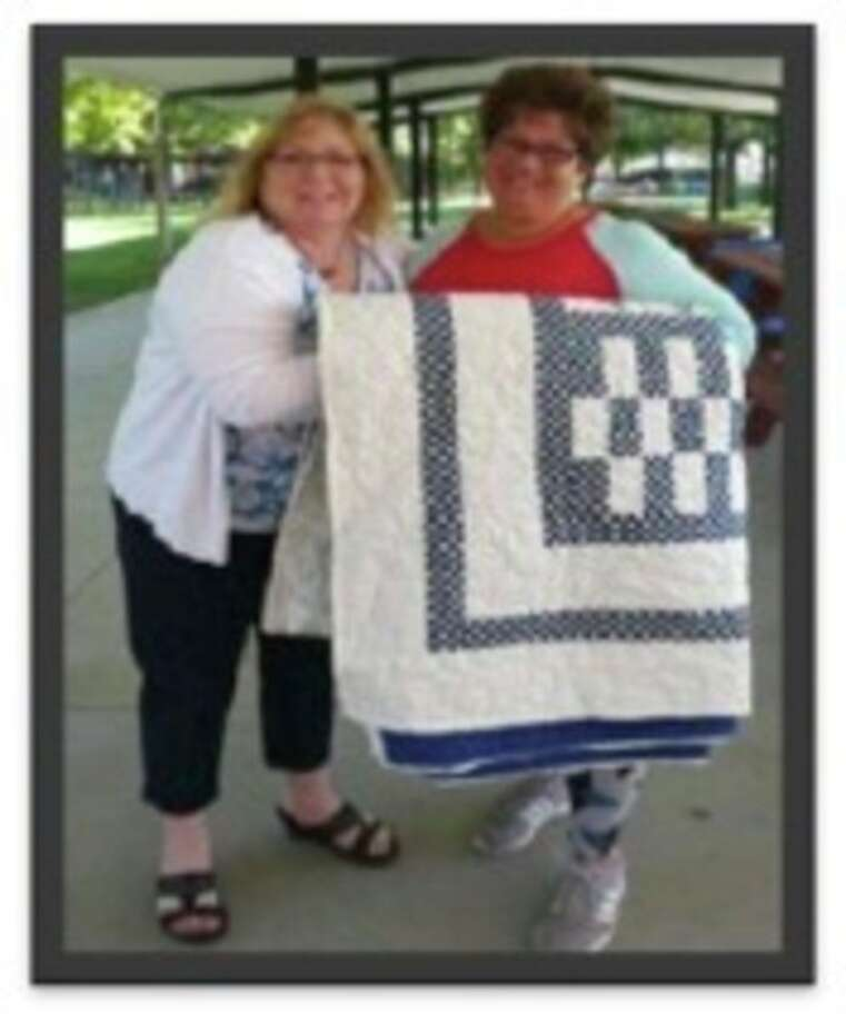 From left, Beth Grossmeyer and Kim Hoeppner pose with the quilt Hoeppner won at the Hemlock Sawdust Days.