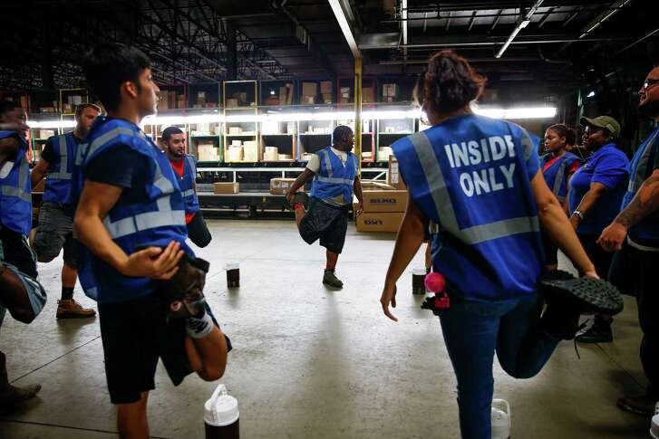 Seasonal UPS workers stretch before heading to work the floor at the UPS Sweetwater hub in Houston.