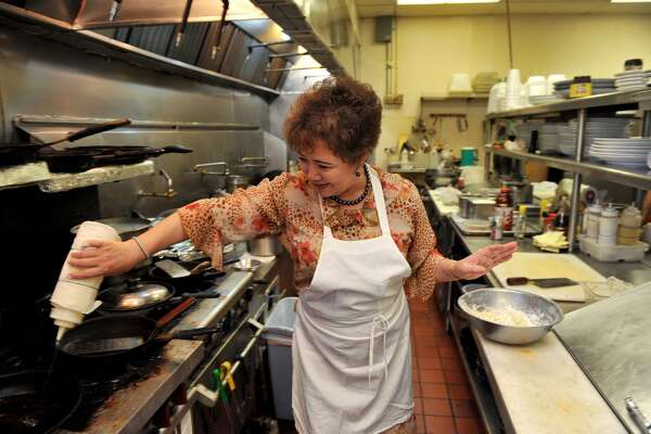 Young Cacy prepares a shrimp vegetable pancake in the kitchen of Ilsong Korean BBQ that she and her husband, Army veteran Tom Cacy own.