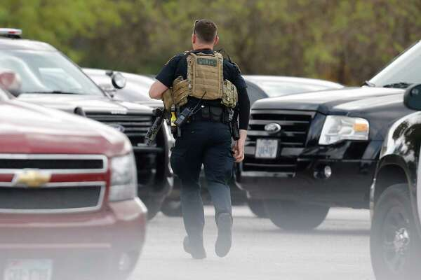A police officer runs through the parking lot near Nordstrom as police responded to reports of gunshots near La Cantera on Thursday, Oct. 13, 2016.