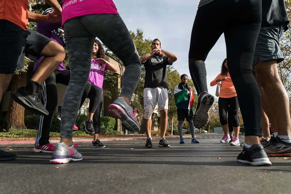 Runners going from Google's Headquarters in Mountain View, Calif. to Apple's Campus in Cupertino stretch on Thursday, Oct. 13, 2016. The runners are protesting the roughly 150 cities on the West Bank that do not appear on Google or Apple maps.