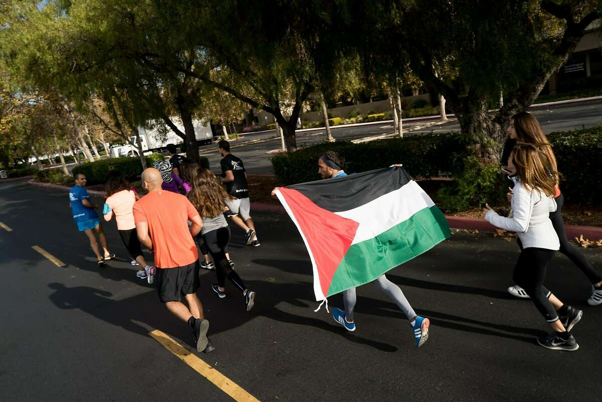 Runners going at Google's Headquarters in Mountain View, Calif. to Apple's Campus in Cupertino begin their run on Thursday, Oct. 13, 2016. The runners are protesting the roughly 150 cities on the West Bank that do not appear on Google or Apple maps.