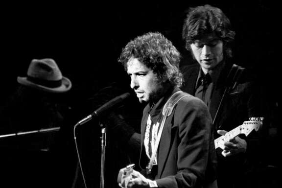 """FILE -- Bob Dylan, left, and Robbie Robertson, guitarist for Dylan's backing band """"The Band,"""" perform at Madison Square Garden in New York, Jan 30, 1974. Dylan, one of the worldé•s most influential rock musicians, was awarded the Nobel Prize in Literature on Oct. 13, 2016, for é'having created new poetic expressions within the great American song tradition,é"""" in the words of the Swedish Academy.  (Larry Morris/The New York Times)"""