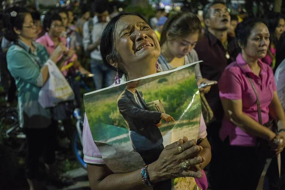 A woman reacts after the death of King Bhumibol Adulyadej outside the hospital where he was being treated in Bangkok. Photo: ADAM DEAN, NYT