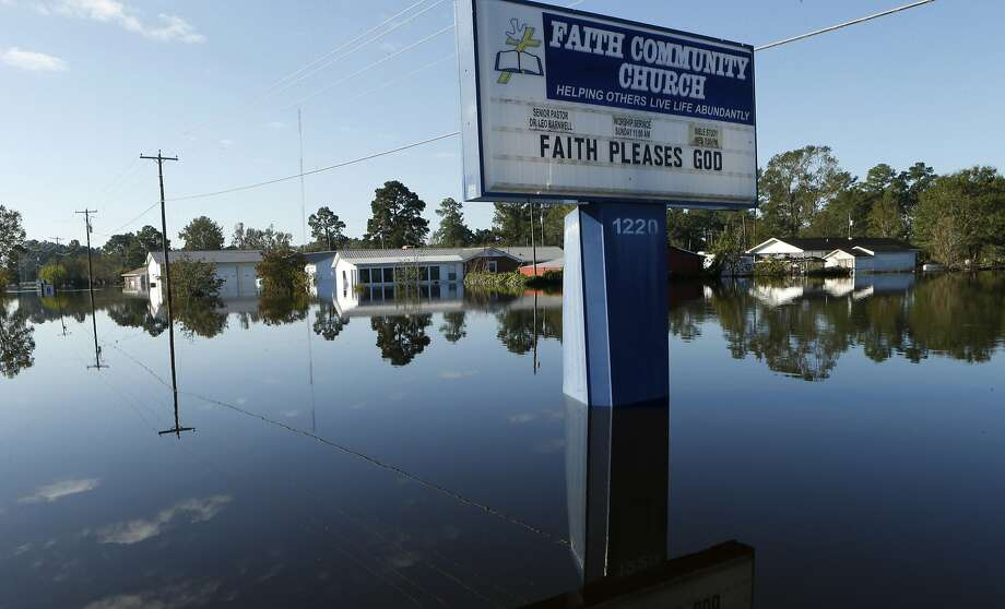 Floodwaters associated with Hurricane Matthew surround homes and a church sign Thursday, Oct. 13, 2016, in Lumberton, N.C.  Gov. Pat McCrory said Thursday the number of power outages was down to about 55,000, from a high of nearly 900,000 when the storm hit last week.  (AP Photo/Brian Blanco) Photo: Brian Blanco, Associated Press