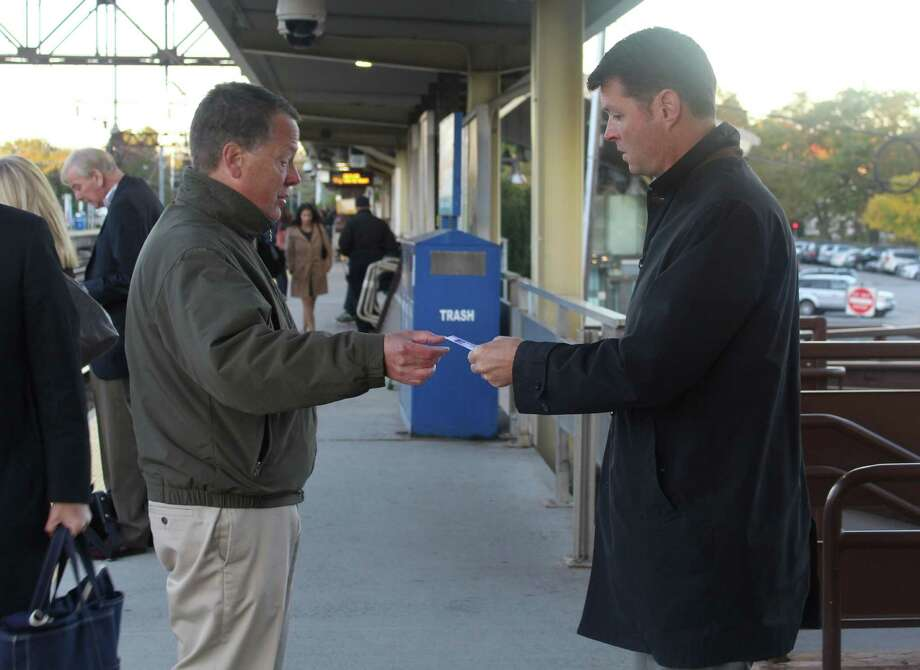 Y's Men Community Service Projects Coordinator Joe Hawley hands domestic violence awareness information to a commuter. Police and Y's Men volunteers gave out Domestic Violence Crisis Center informational cards and help resources at the Westport Train Station in Westport, Conn. on the morning of Oct. 11, 2016. Photo: Laura Weiss / Hearst Connecticut Media / Westport News