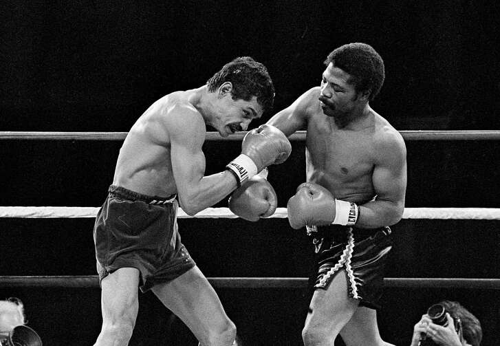 Alexis Arguello (left) covers up as defending champ Aaron Pryor throws a hard right during the second round of boxing action at the Orange Bowl in Miami on Nov. 12, 1982.