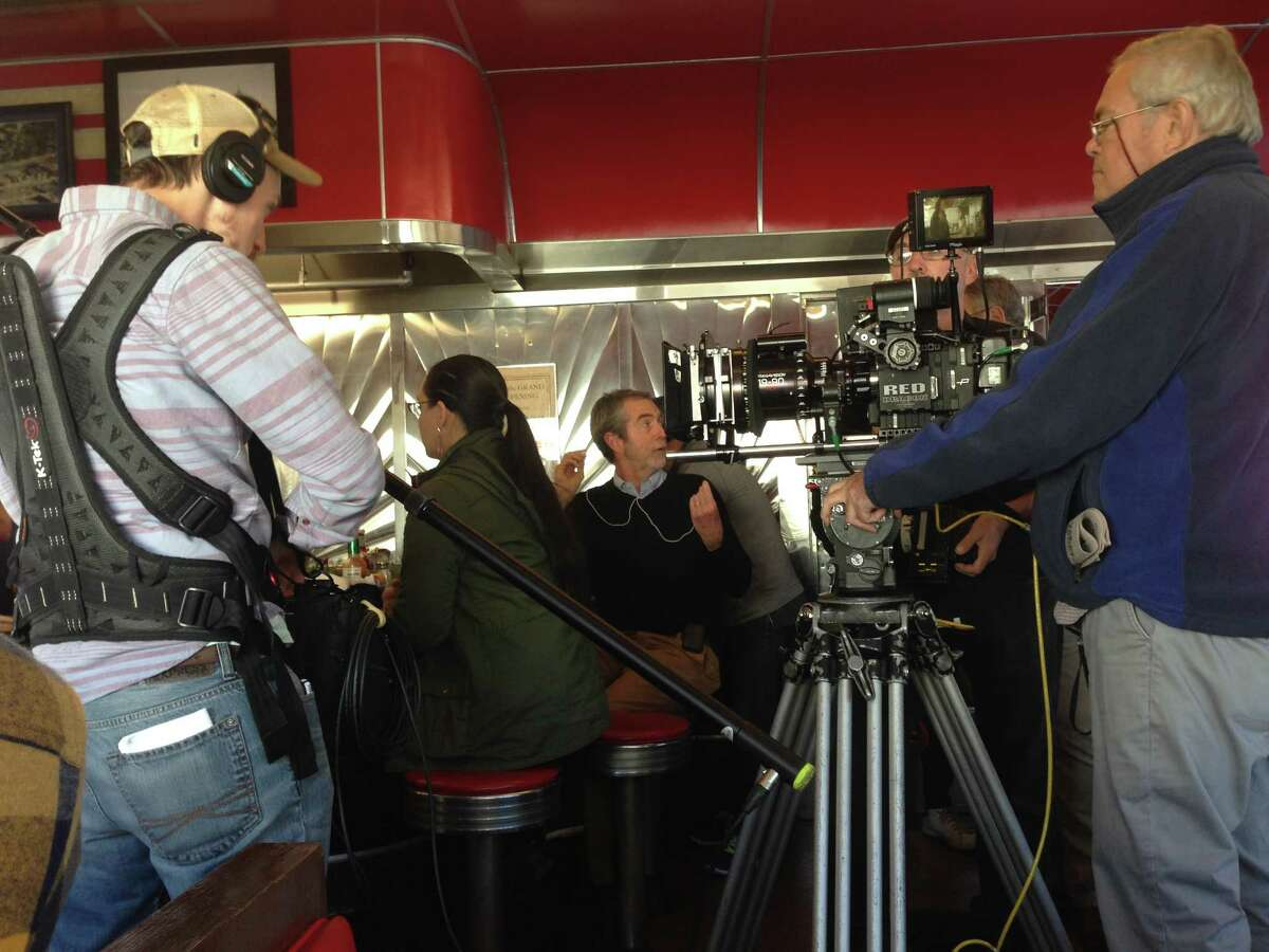 """Director David Jackson, center, and cameraman Denis Mahoney, right, shooting """"Derailed"""" at Jack's Diner in Albany (photo by Amy Biancolli)"""