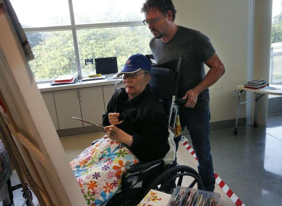 Art Instructor Mark Campbell moves Tony Yu, 93, as Yu works on a painting during a class at Laguna Honda Hospital and Rehabilitation Center. Photo: Leah Millis, The Chronicle