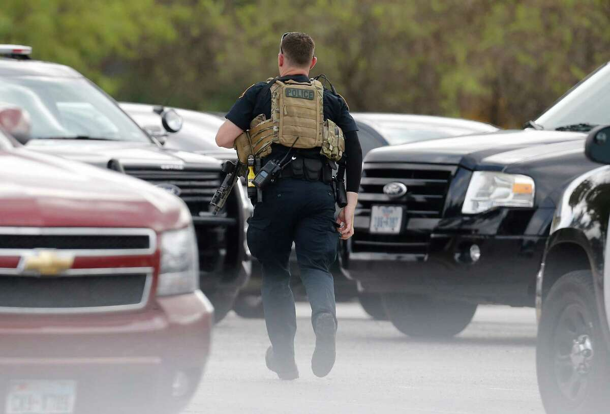 A police officer runs through the parking lot near Nordstrums, Thursday, Oct. 13, 2016, after there were reports of shots fired at passing vehicles in the northwest neighborhood of San Antonio.
