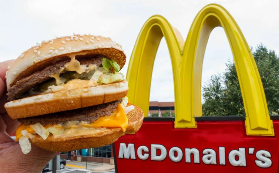 A Big Mac is held up near the golden arches at a McDonalds's. Photo: PAUL J. RICHARDS, AFP/Getty Images