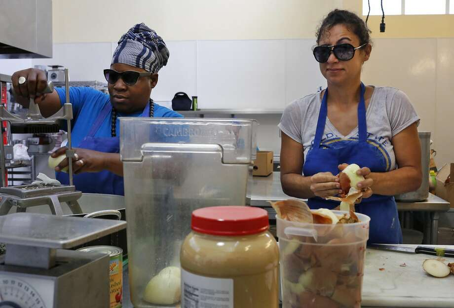 Reem Assil (right) grimaces as she and Wanda Kruda wear sunglasses to protect their eyes while they prepare onions at La Cocina incubator kitchen in San Francisco. Photo: Leah Millis, The Chronicle